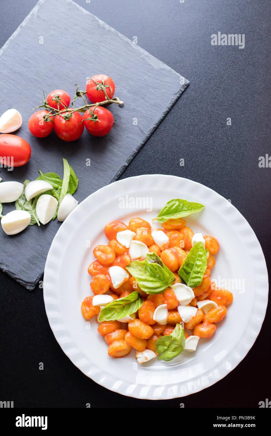 Alla Sorrentina gnocchi de pommes de terre à la sauce tomate avec du basilic vert et boules de mozzarella servi sur une assiette et les ingrédients sur conseil de schiste noir sur b Banque D'Images