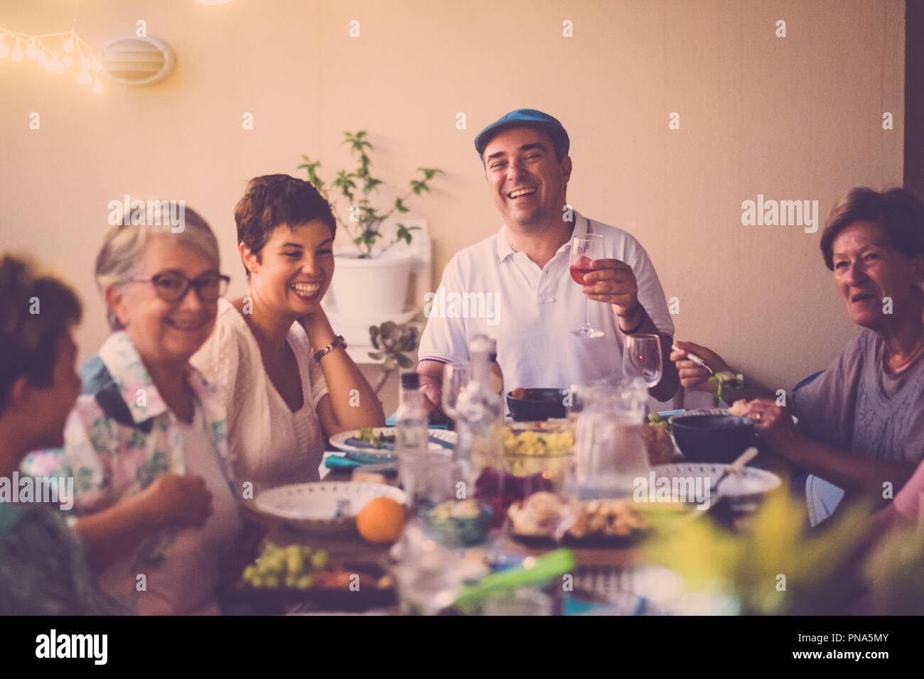 Happy group d'âges différents gens célébrer et s'amuser ensemble dans l'amitié à la maison ou au restaurant. Acclamations et grillage avec cocktails et Photo Stock