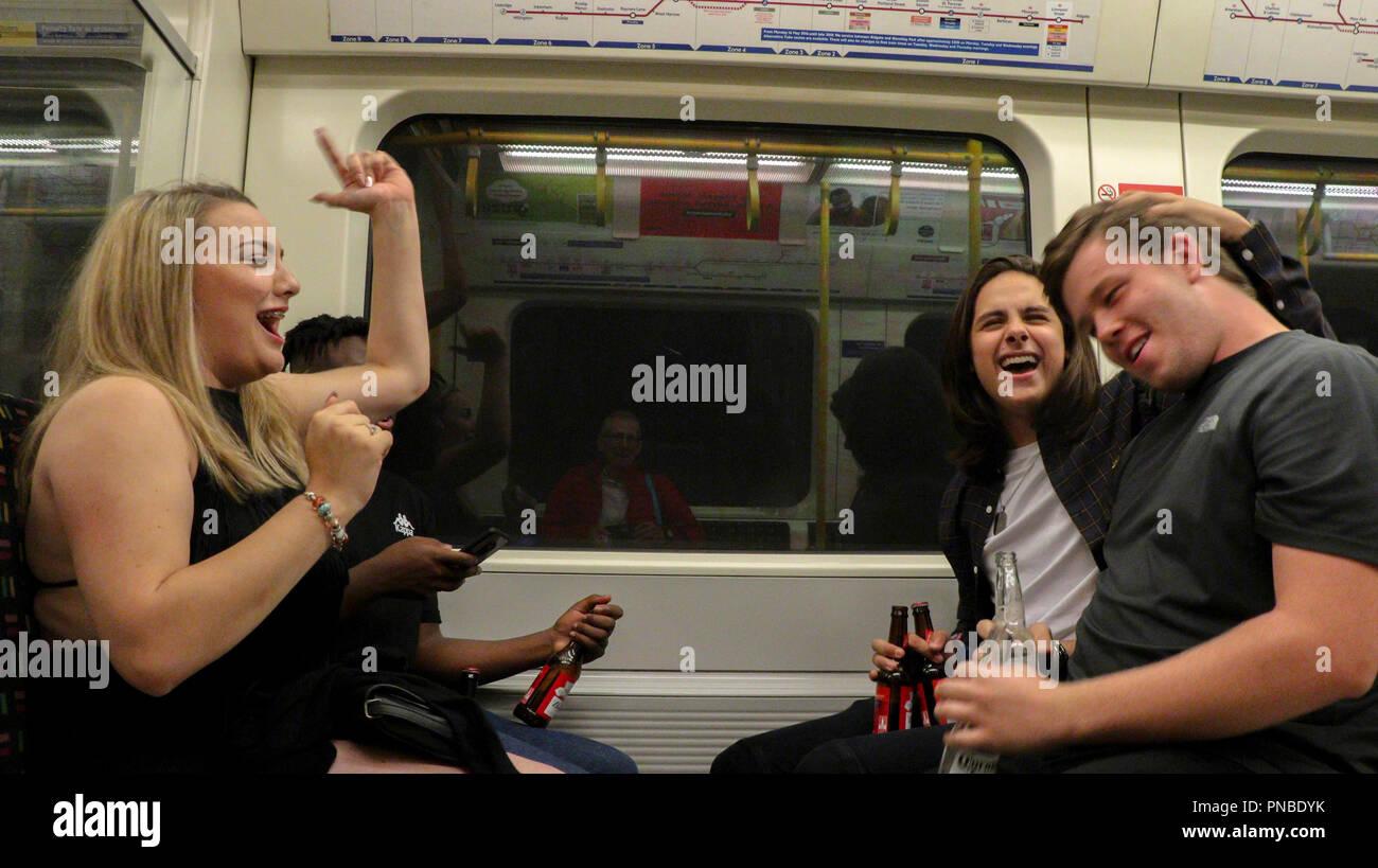 Les passagers à faire la fête avec les bouteilles de bière, métro de Londres, Angleterre, RU Photo Stock