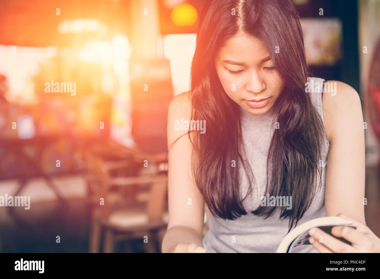 Profitez de moments de détente avec lecture du livre, la femme asiatique teen thaï à l'accent grave lire livre de poche dans un café le matin, le ton des couleurs vintage Photo Stock