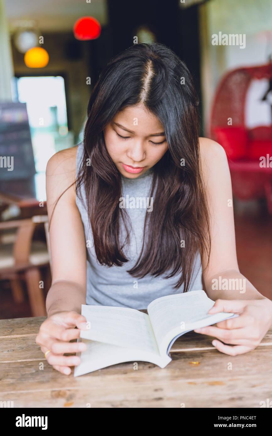 Profitez de moments de détente avec lecture du livre, la femme asiatique teen thaï à l'accent grave lire livre de poche dans un coffee shop. Photo Stock