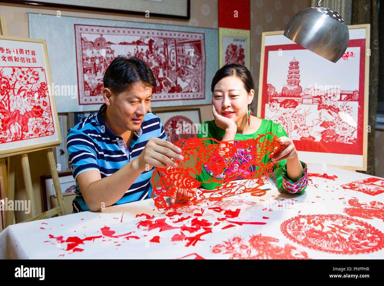 (180921) -- SHANGHAI, 21 septembre 2018 (Xinhua) -- Papercutting artiste Qiu Ting et son mari Qiu Hanping regardez une récolte-themed papercutting à Shanghai, ville de la province de Shandong, Chine orientale, le 17 septembre 2018. Qiu a passé plus de deux mois dans la création d'un 2 018 centimètres de long papercutting pour accueillir le premier festival de la récolte des agriculteurs chinois, qui tombe sur l'Équinoxe, ou 23 septembre cette année. (Xinhua/Chanson Haicun) (hxy) Photo Stock