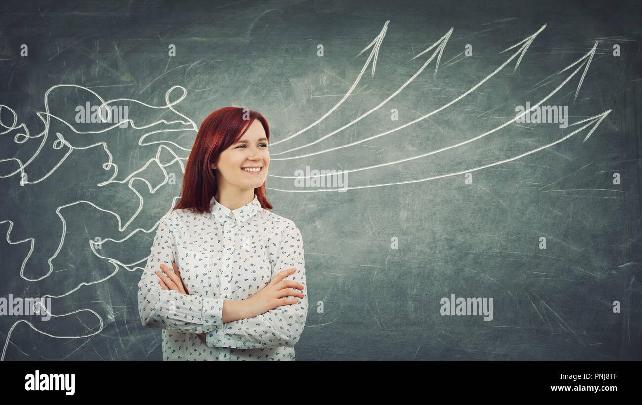 Concept de traitement de l'information comme un concentré redhead woman smiling in avant d'un immense tableau noir comme lignes de maillage venir par tête et transformer Photo Stock