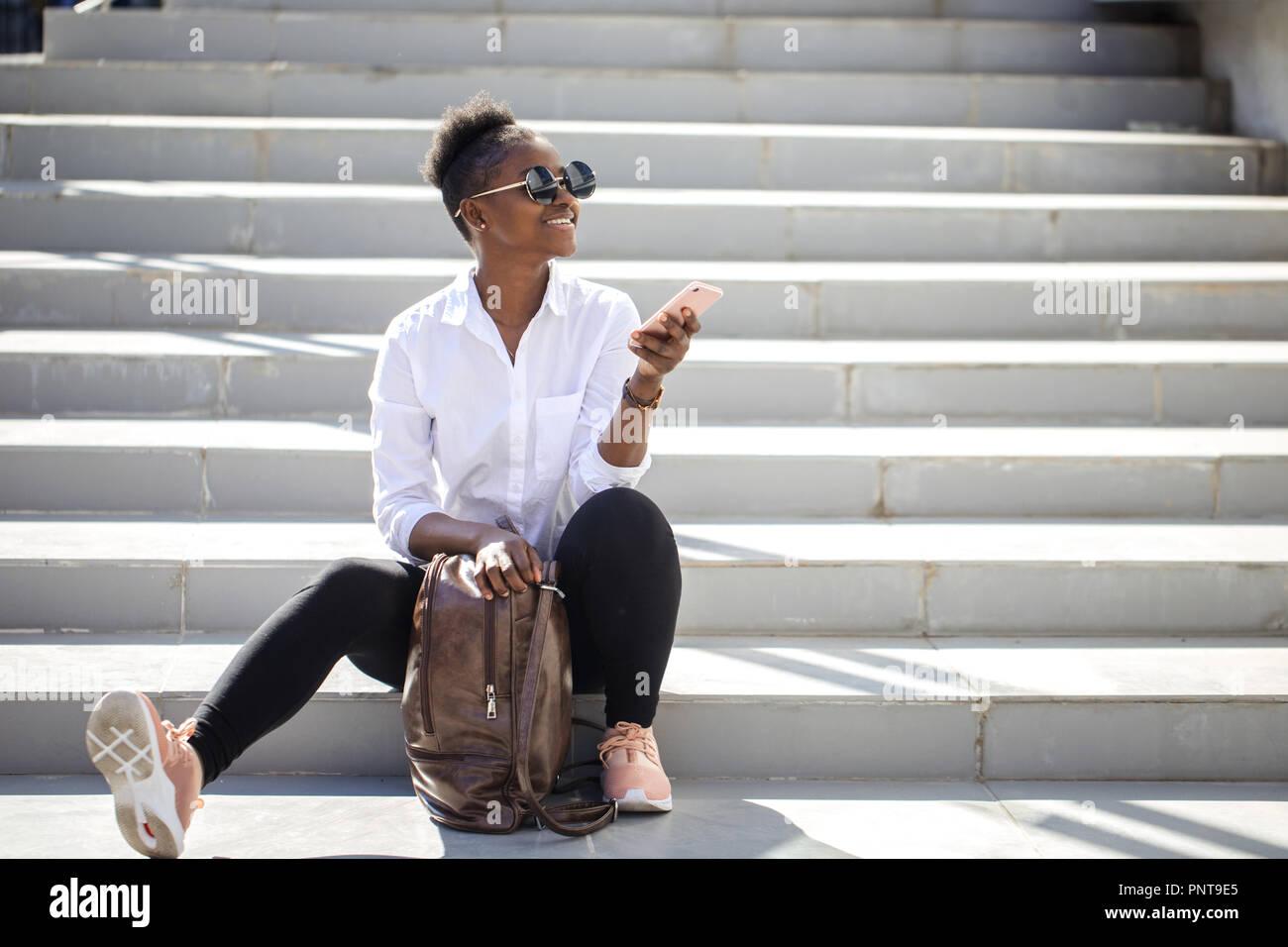 Femme africaine à l'aide de smart phone, assis sur un escalier blanc à l'extérieur. Photo Stock