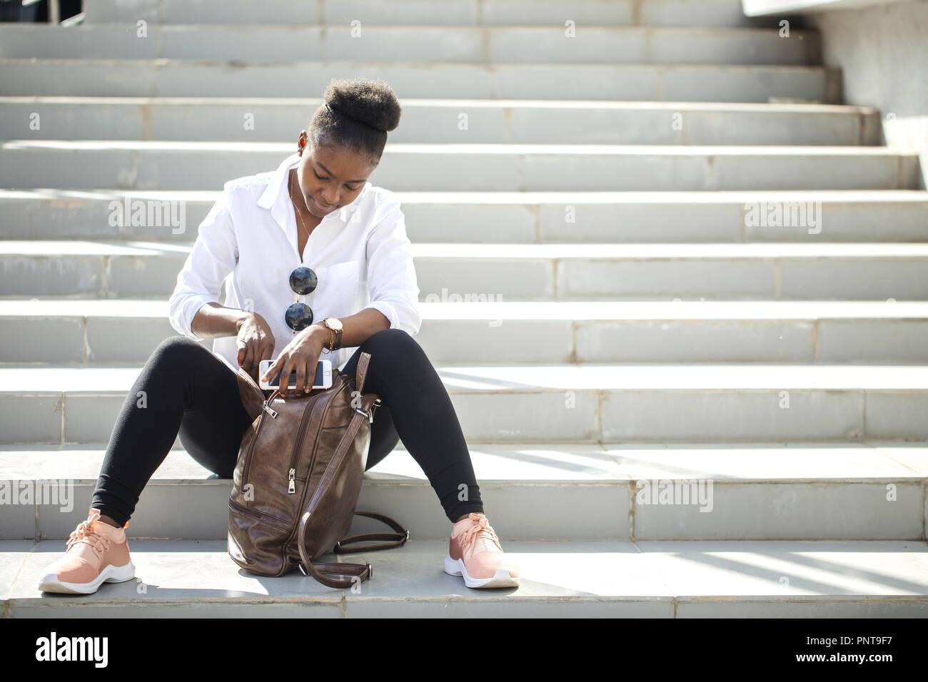 Femme africaine à l'aide de smart phone, assis sur un escalier blanc à l'extérieur. Banque D'Images