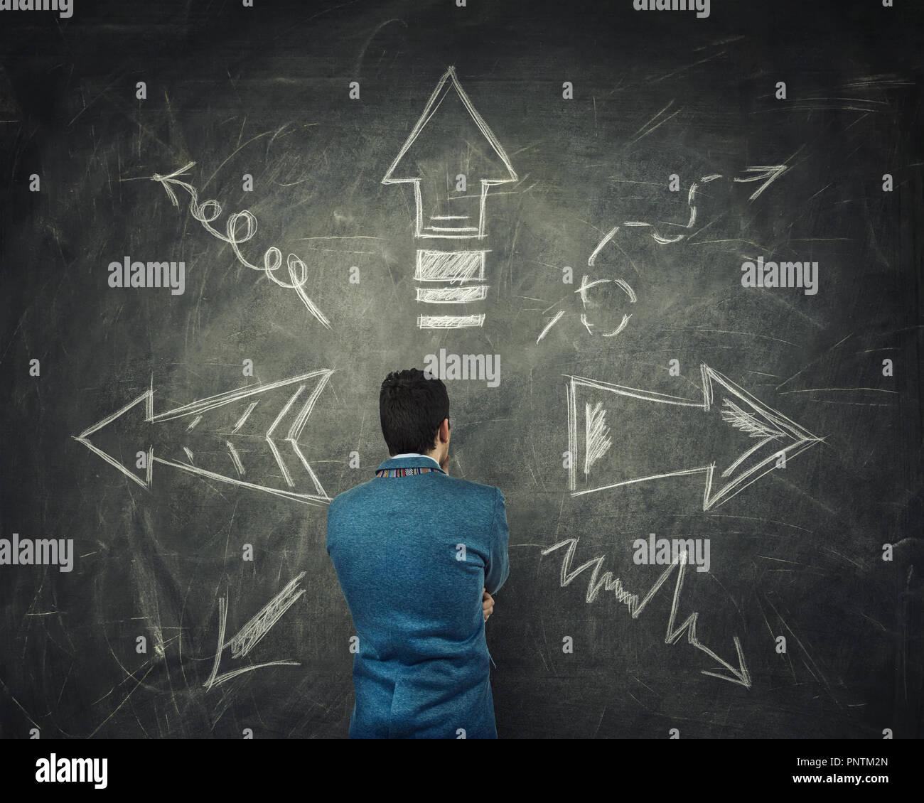 Vue arrière du pensive businessman thinking in front of a grand tableau noir avec des flèches a fait à des directions différentes. Choix difficile, décide quels wa Photo Stock