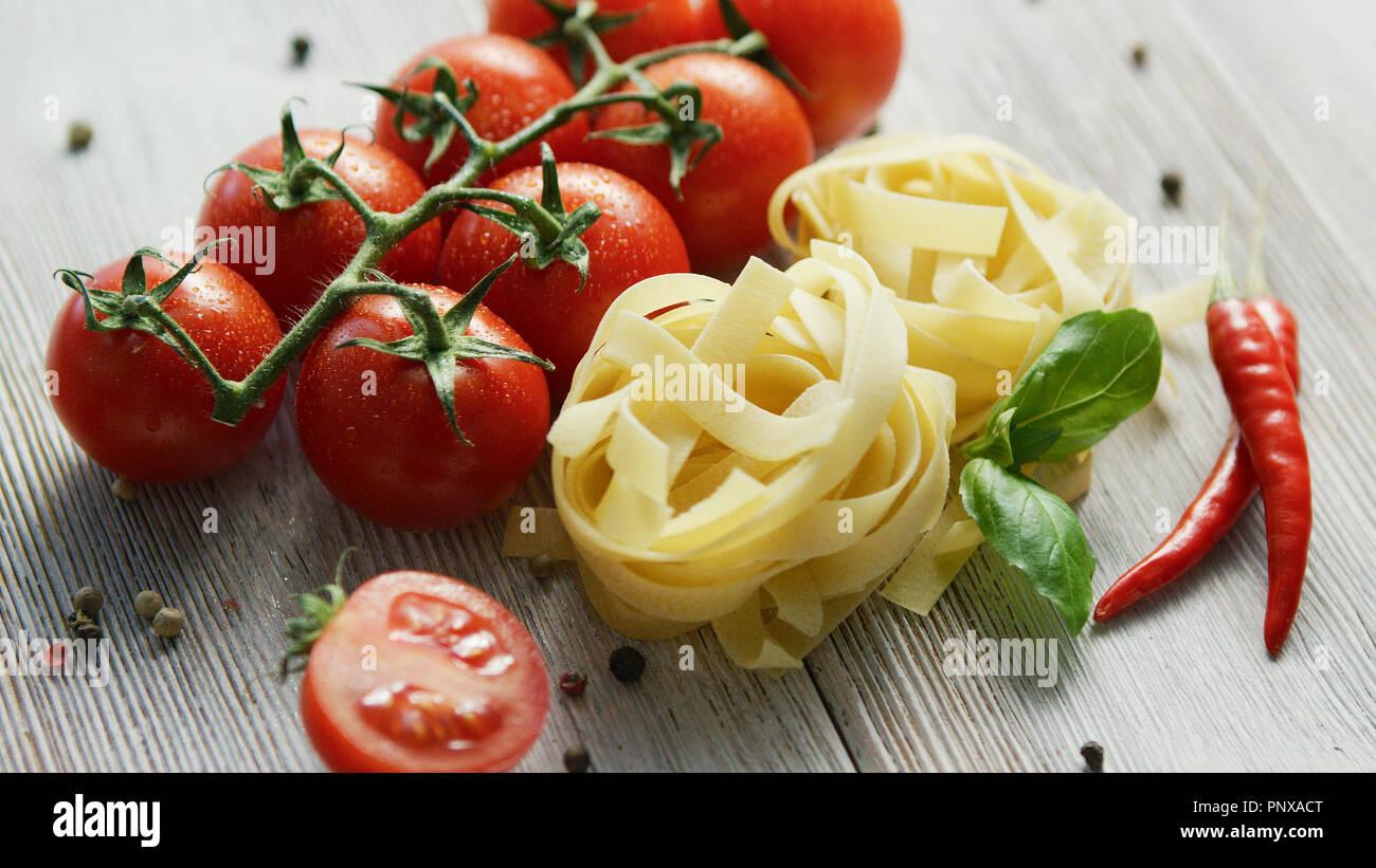 Pâtes alimentaires non cuites avec des tomates grappes Photo Stock