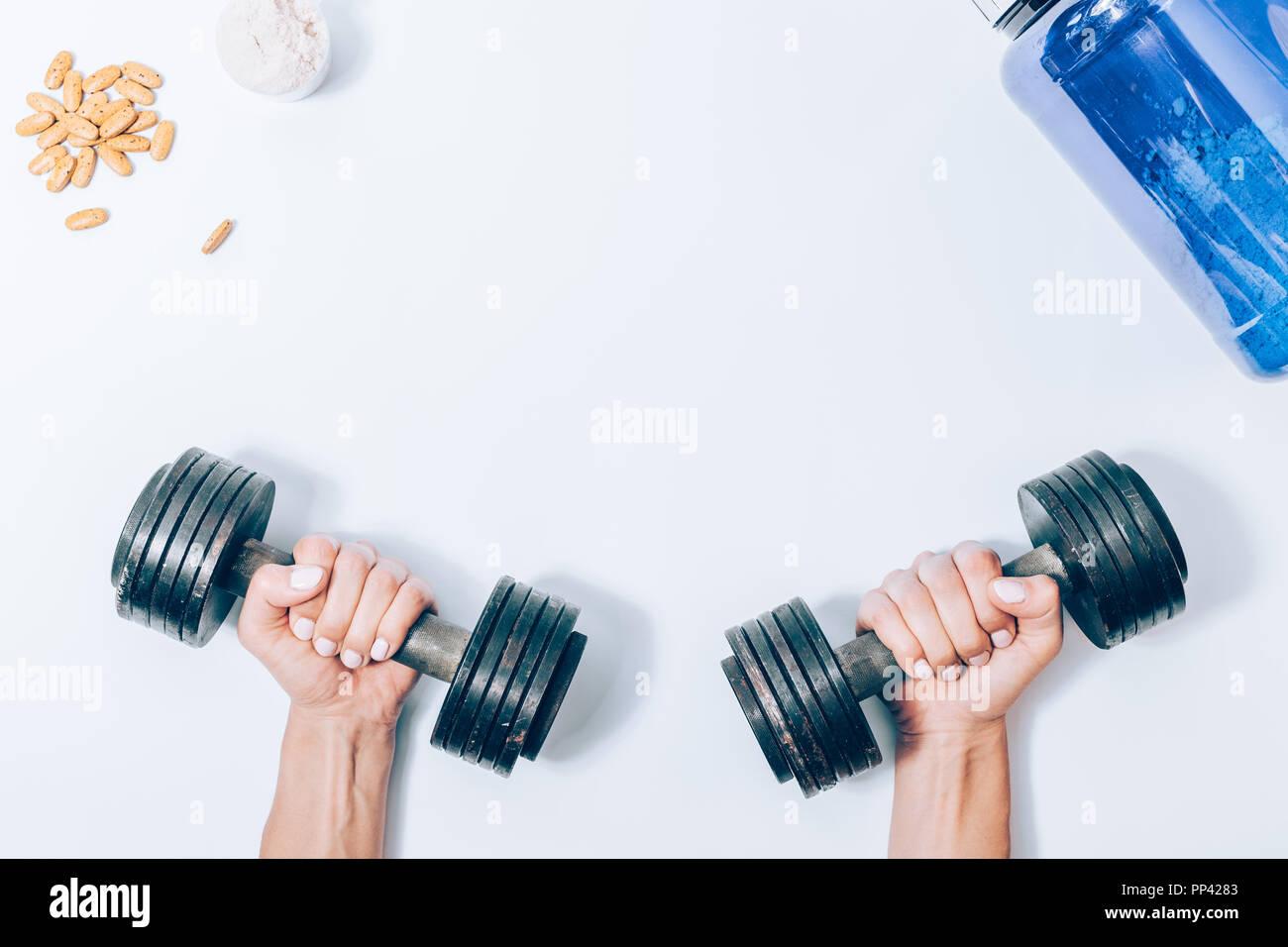 Télévision femme modèle mains tenant des haltères en métal à côté de la protéine en poudre et de vitamine comprimés, vue du dessus. Concept de l'amélioration de la force corporelle à l'aide de lourdes nous Banque D'Images