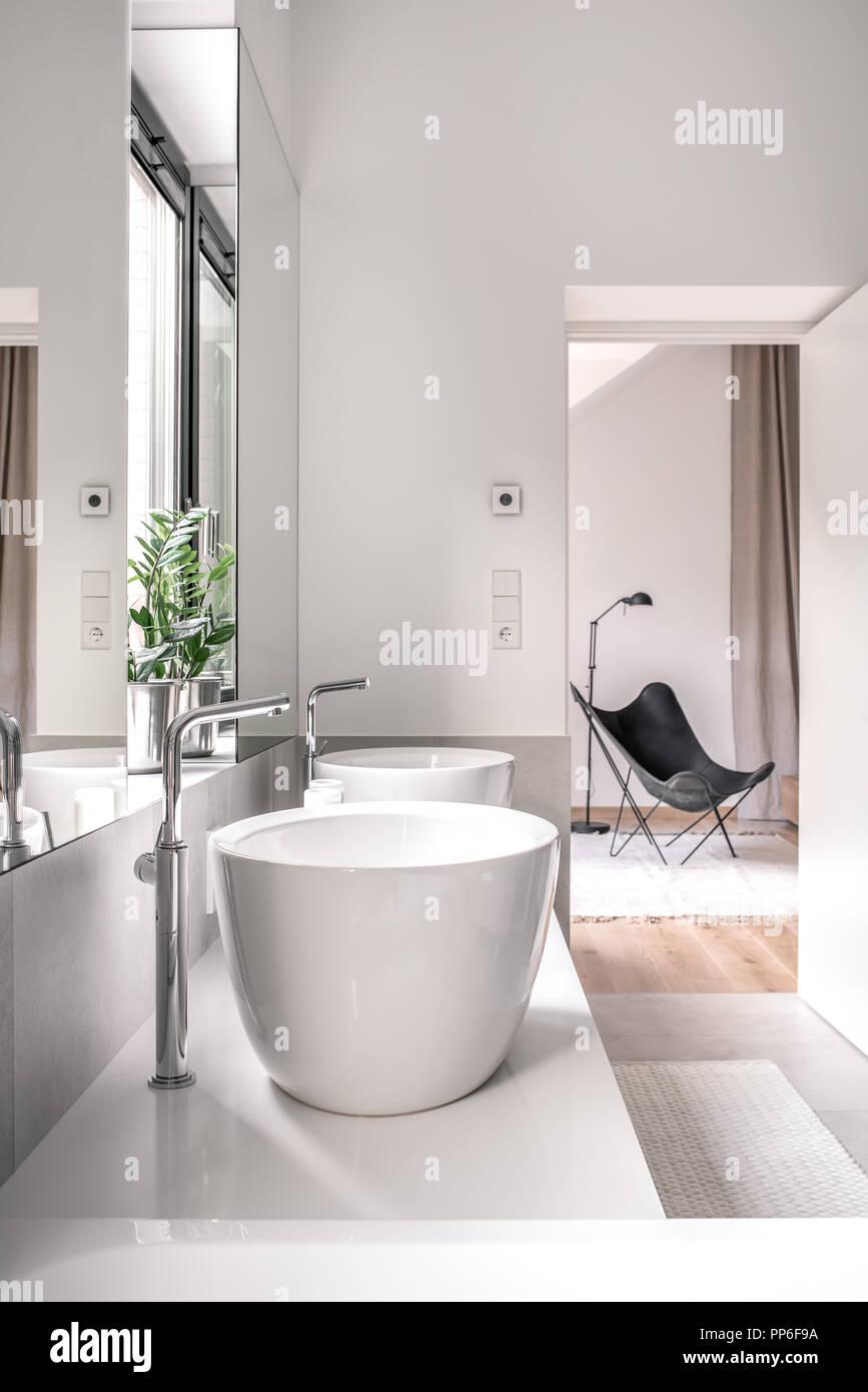 Salle de bains moderne avec sol carrelé blanc et de murs gris. Il y ...