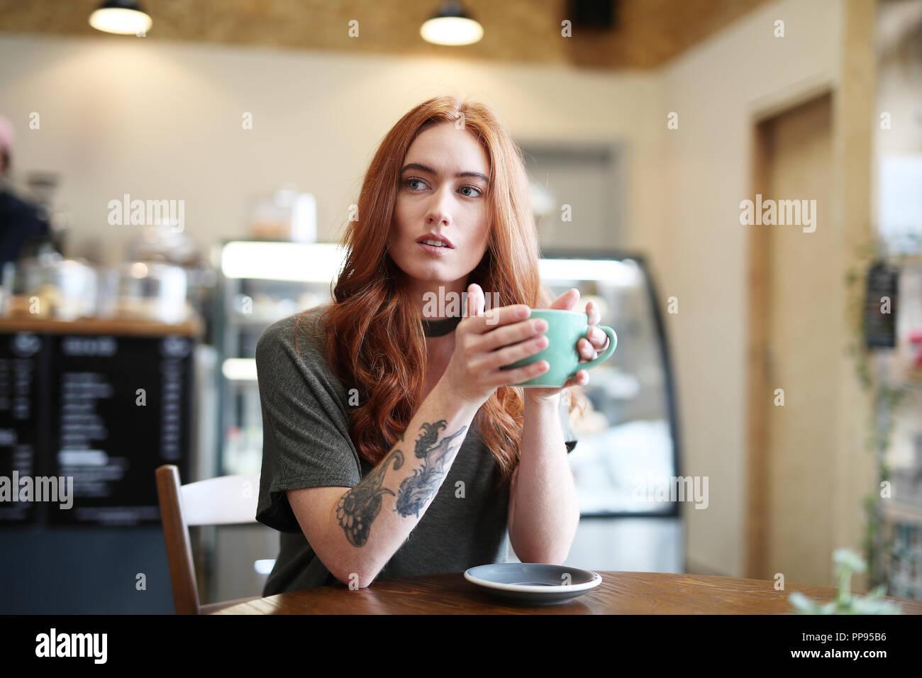 Une femme avec un tatouage bras est assis à une table en bois tenant une tasse de Cappuccino dans un bol vert Banque D'Images