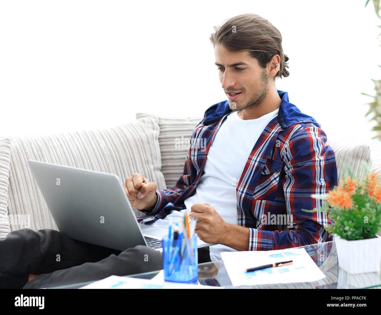 Surpris jeune homme travaillant avec un ordinateur portable à la maison.  Photo Stock 861e32ee0f89