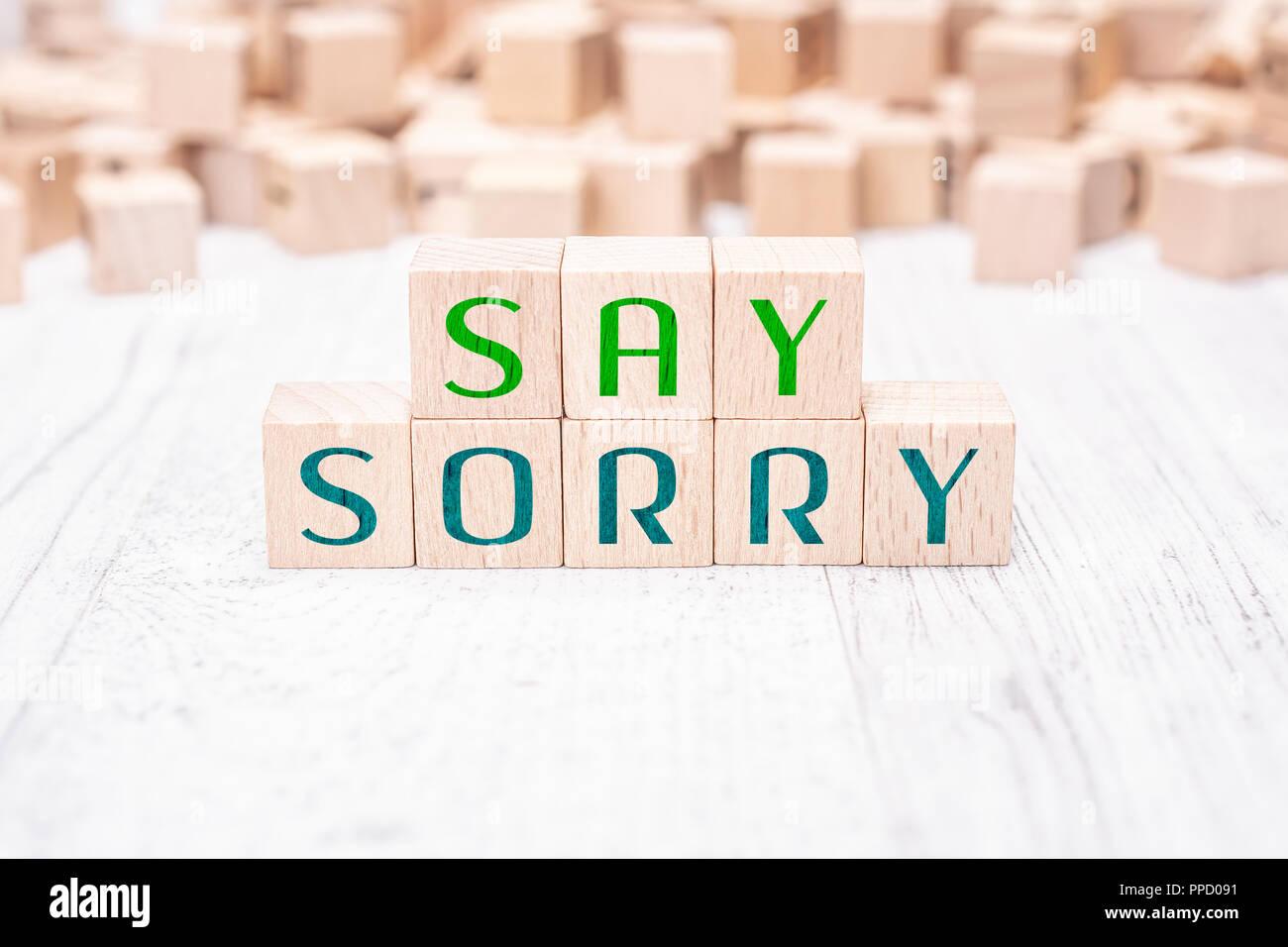 Les mots dire désolé formé par des blocs de bois sur un tableau blanc Photo Stock