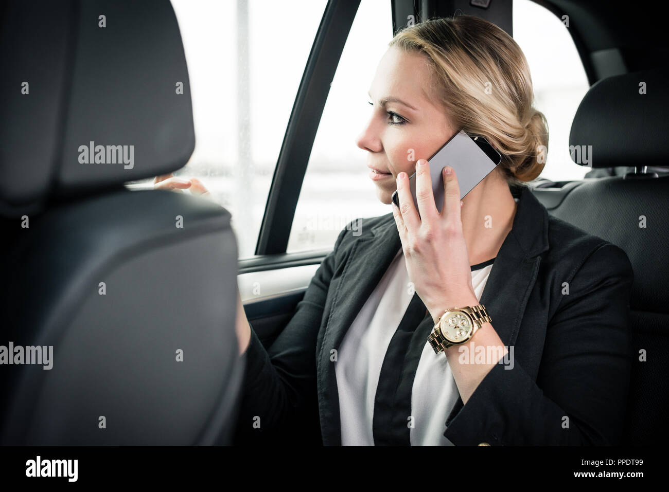 Businesswoman sitting in car talking on cellphone Photo Stock