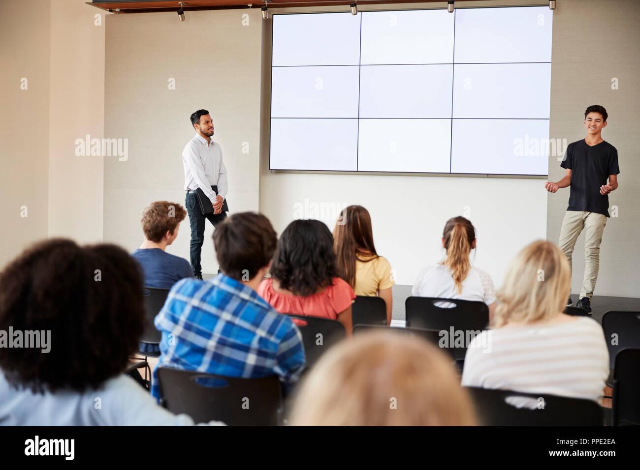 Male Student Giving Presentation de High School Class en face de l'écran Banque D'Images