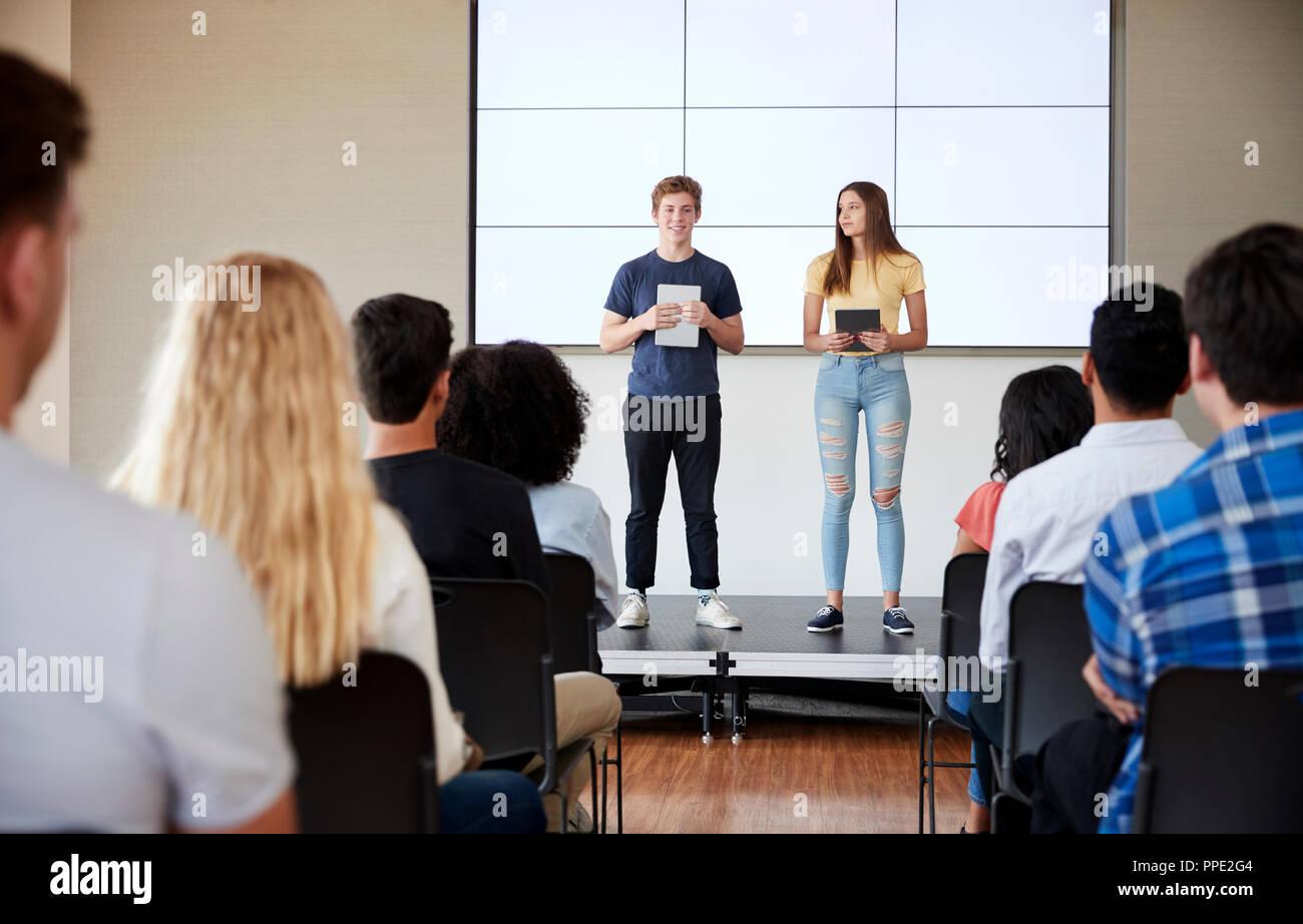 Les élèves ayant des tablettes numériques Présentation donnant à l'école secondaire en classe d'affichage Banque D'Images