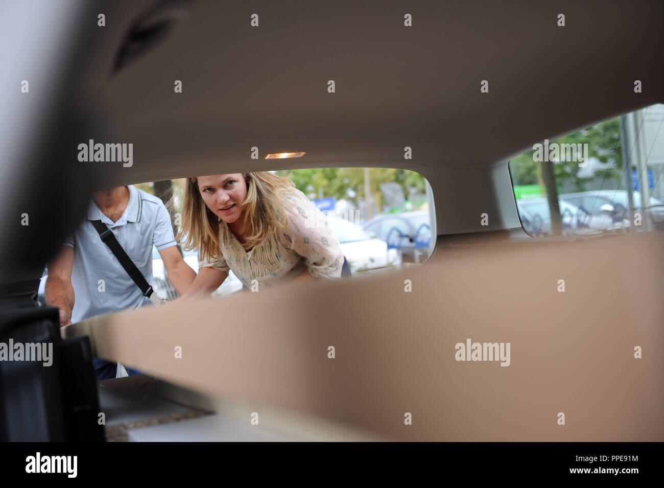 Un couple d'essayer de rentrer leurs achats Ikea dans la voiture. Photo Stock