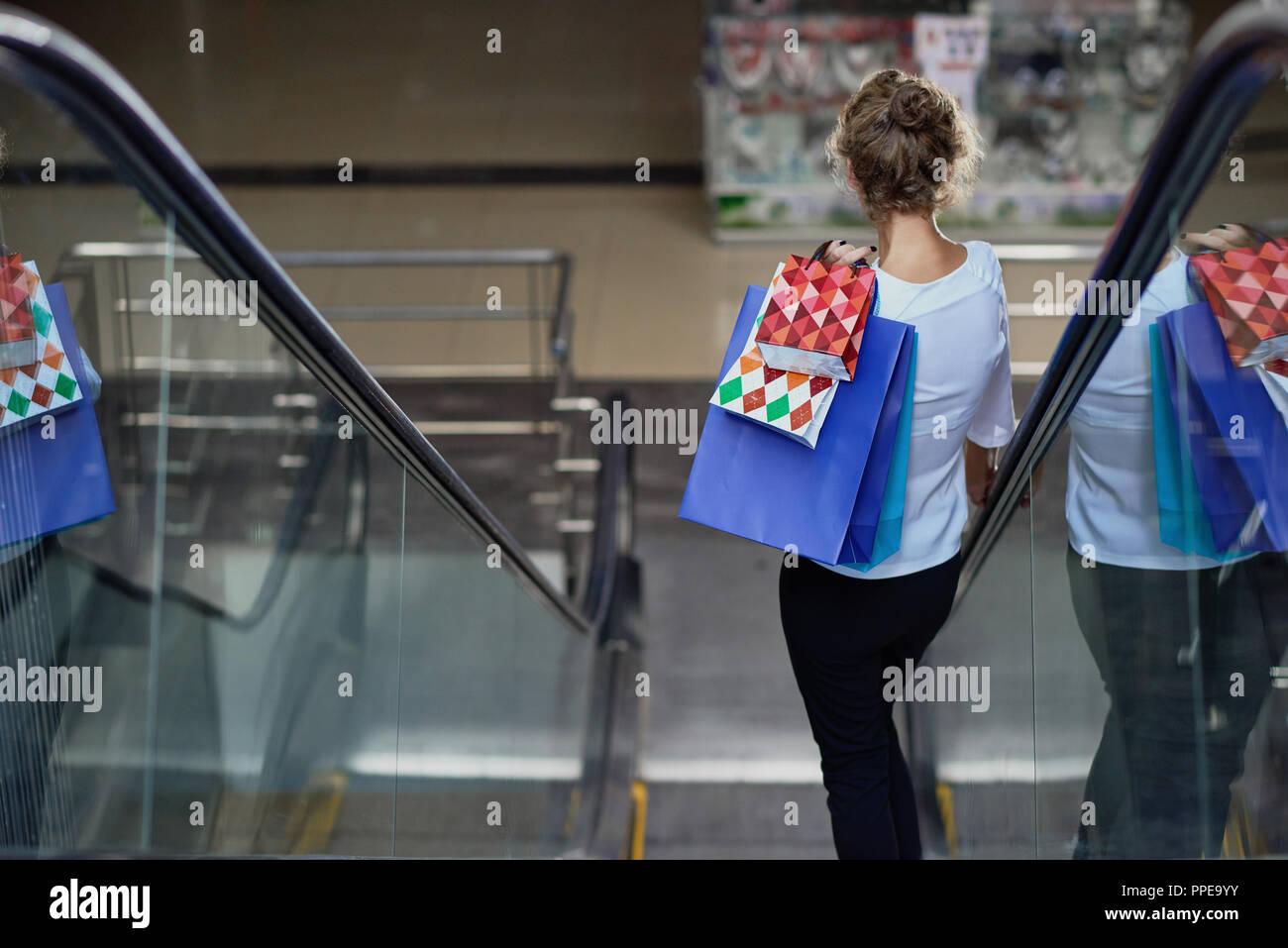 Vue de l'arrière de la clientèle féminine avec des sacs à la baisse sur l'escalator dans centre commercial. Dame bouclés bénéficiant de bonnes boutiques et des nouveaux achats. Concept de l'achat et le plaisir. Photo Stock
