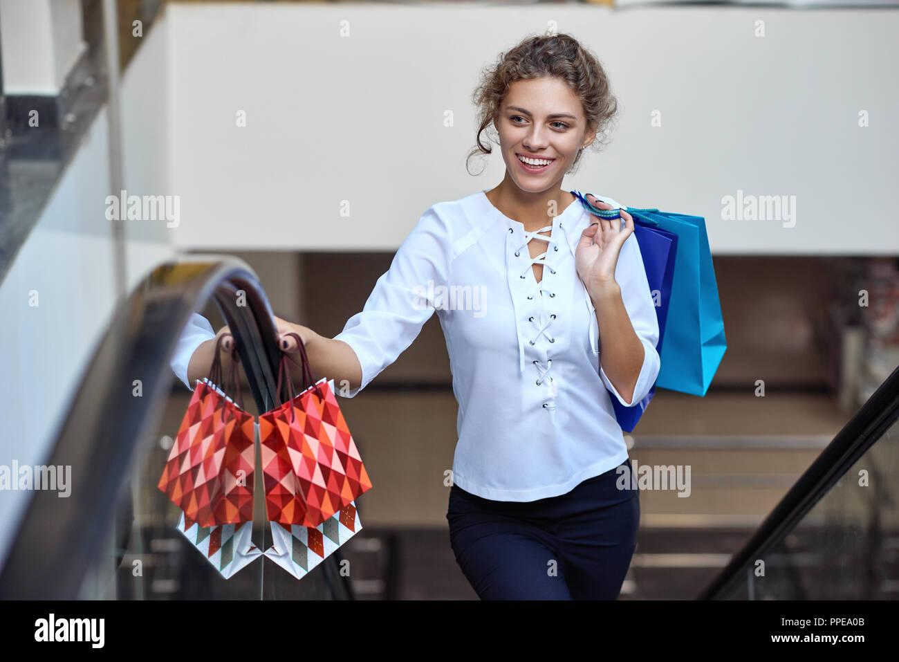 Portrait of happy blonde après bon shopping la voiture dans l'escalator mall. Belle femme avec des sacs de shopping et achats de sourire et à la voiture. Notion de plaisir et de bonheur. Photo Stock