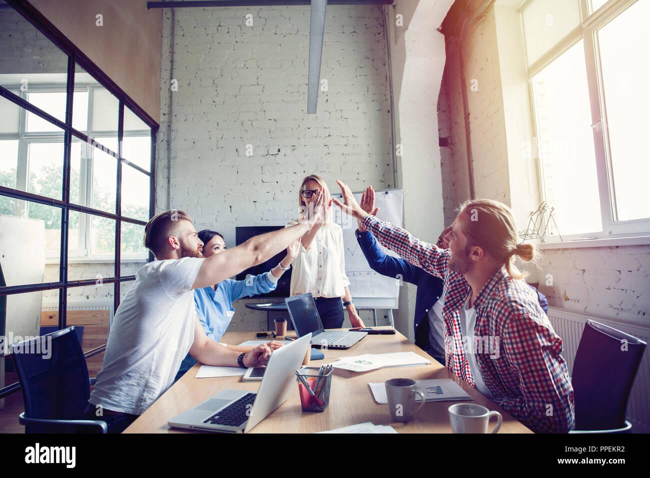 L'équipe entreprise multiraciale réussie heureux donnant une forte fives geste comme ils rient et applaudir leur succès. Photo Stock