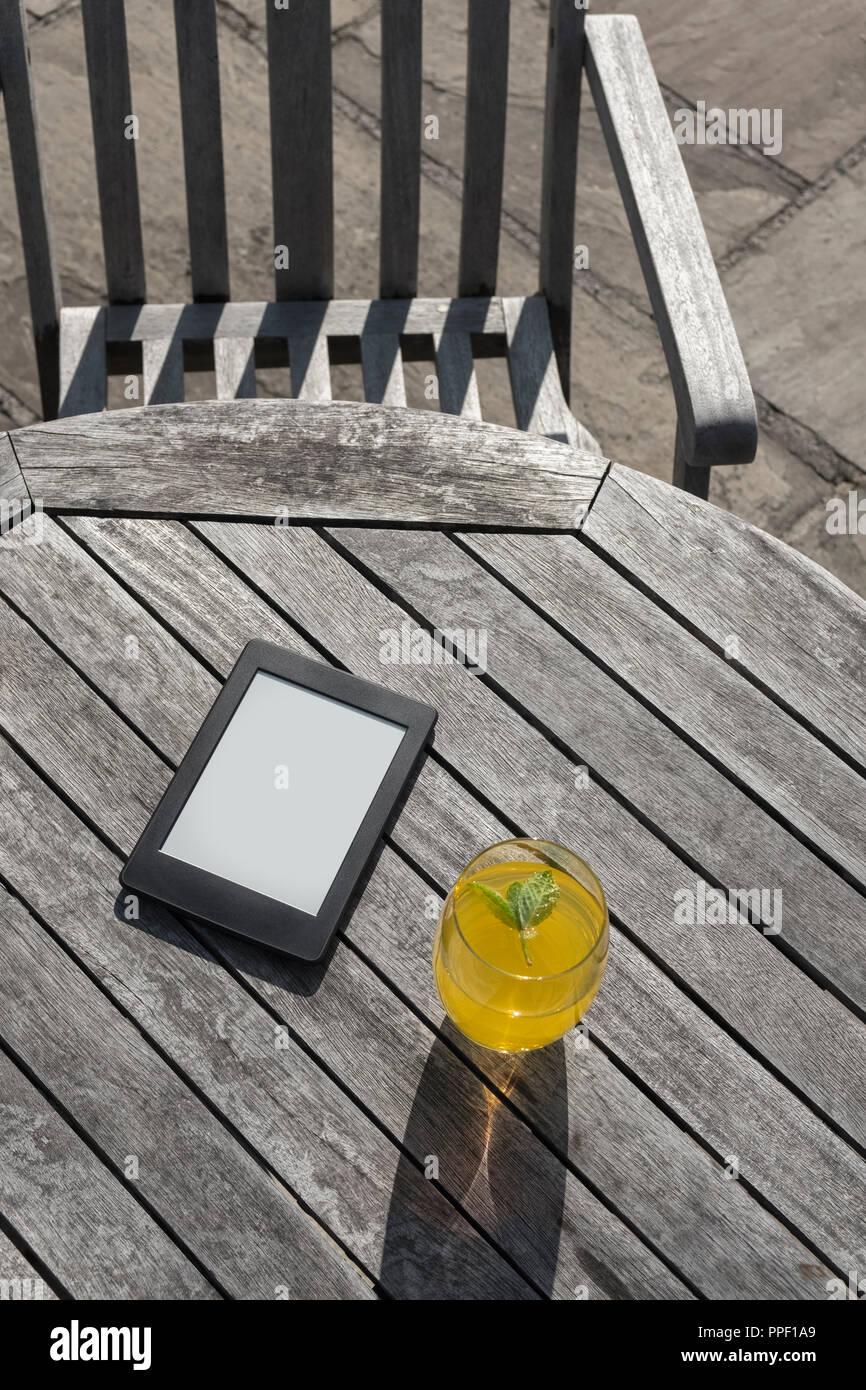 E-reader et un verre de boisson aux fruits sur une table en bois. Photo Stock