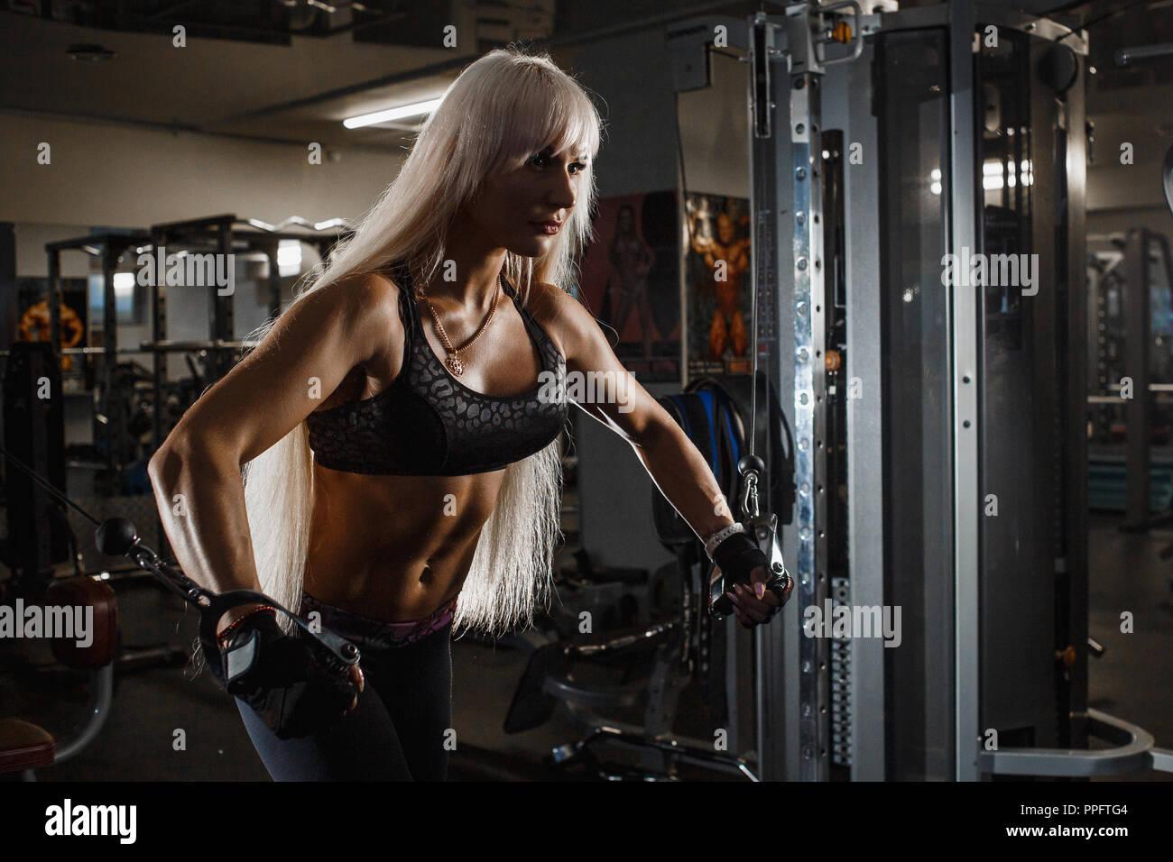 Les jeunes de la formation sportive musculaire avec simulateur de bloc en salle de sport, de travailler dur pour les muscles des bras forts. Jeune fille à la recherche de l'avant la poussée des mains sur les côtés. Sid Banque D'Images
