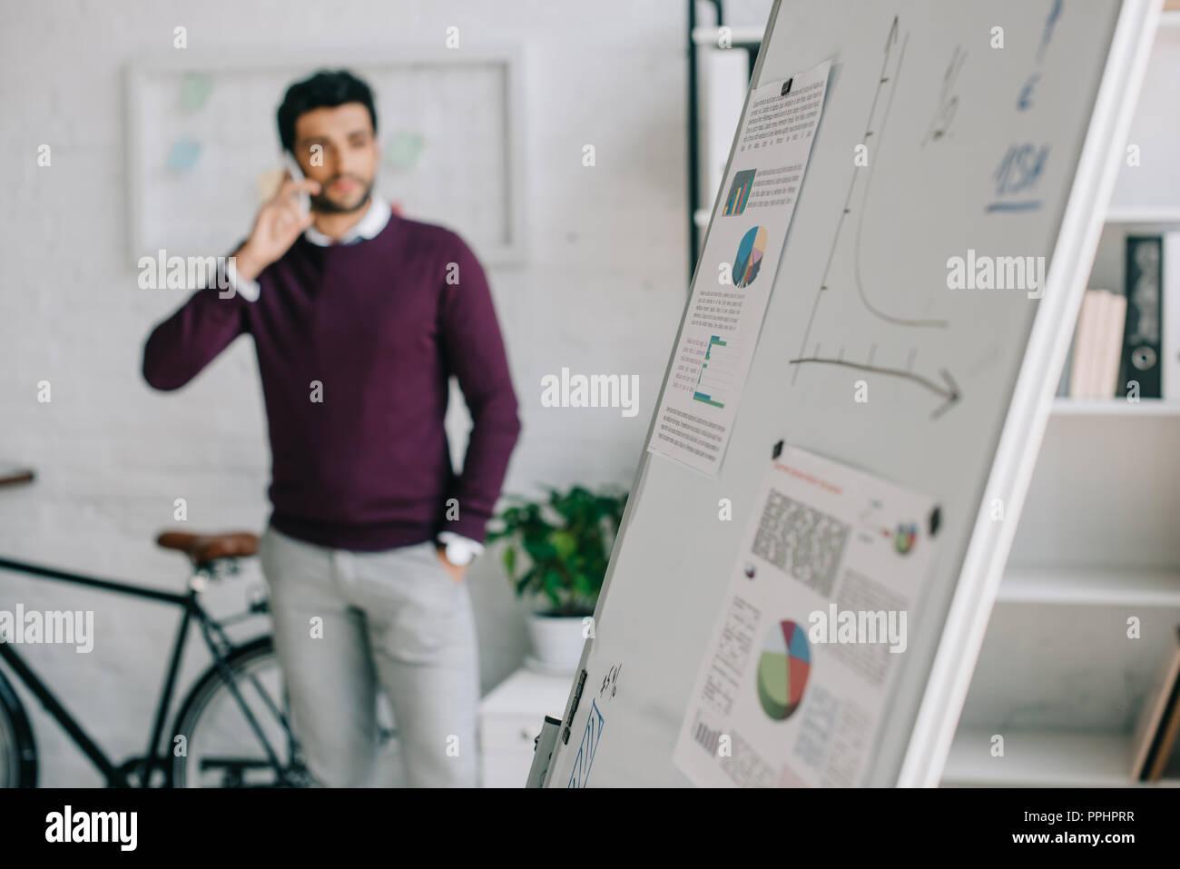 Designer beau chandail en bourgogne en parlant de smartphone avec chevalet de bureau sur le premier plan Photo Stock