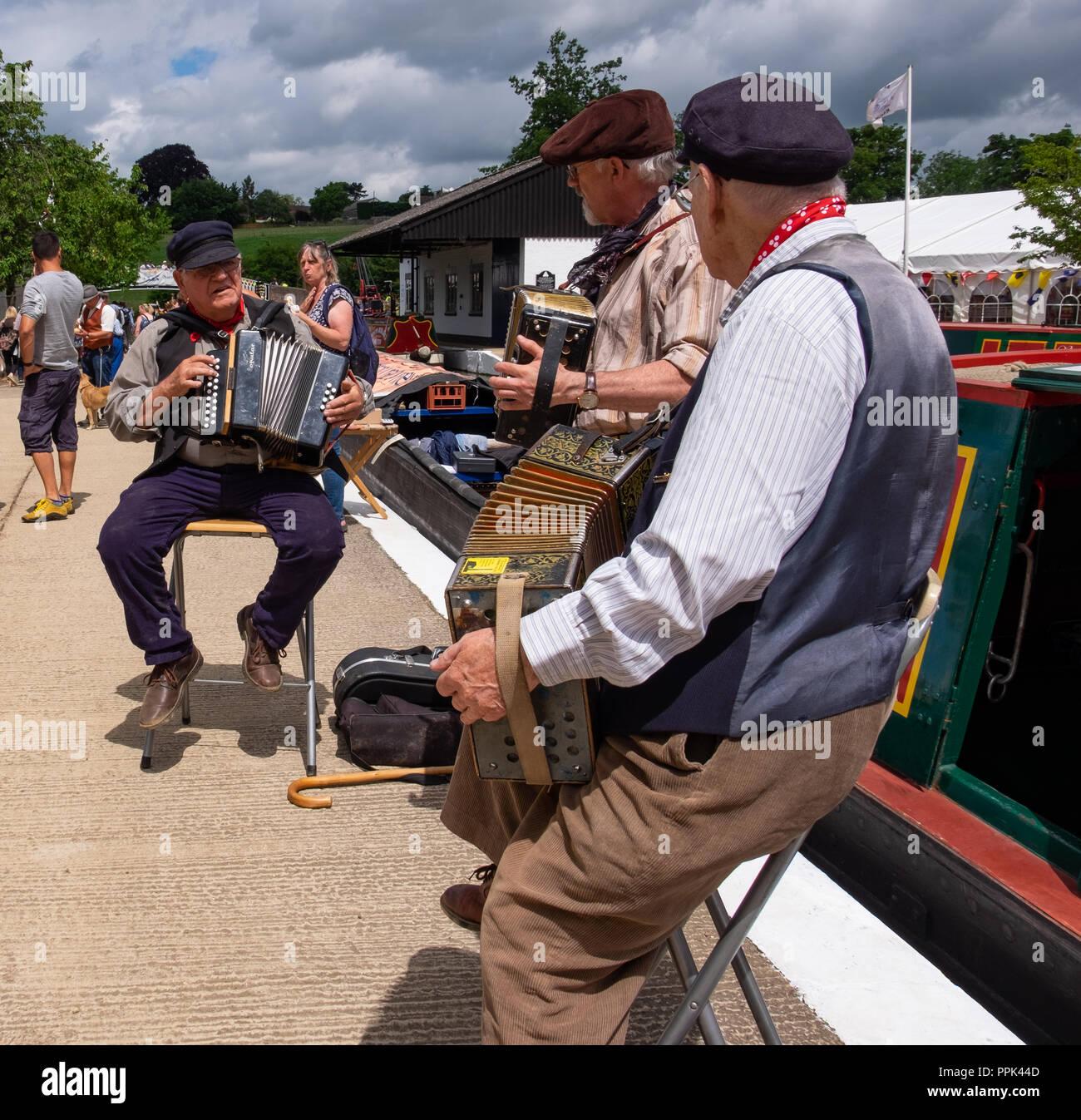 Trois hommes déjà en majuscules dans un style traditionnel costume playing accordion et presser les cases à côté des bateaux du canal sur le canal. Photo Stock