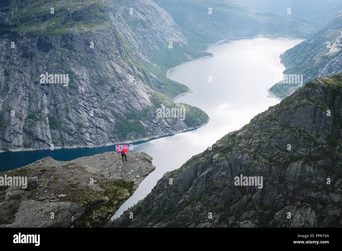 Trolltunga - Cliff rock, au-dessus du lac Ringedalsvatnet en Norvège. Touriste avec pavillon norvégien Banque D'Images