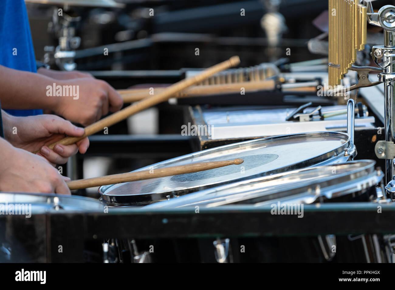 Le clignotement d'un percussionniste pilons sideline à marching band rehearsal Banque D'Images
