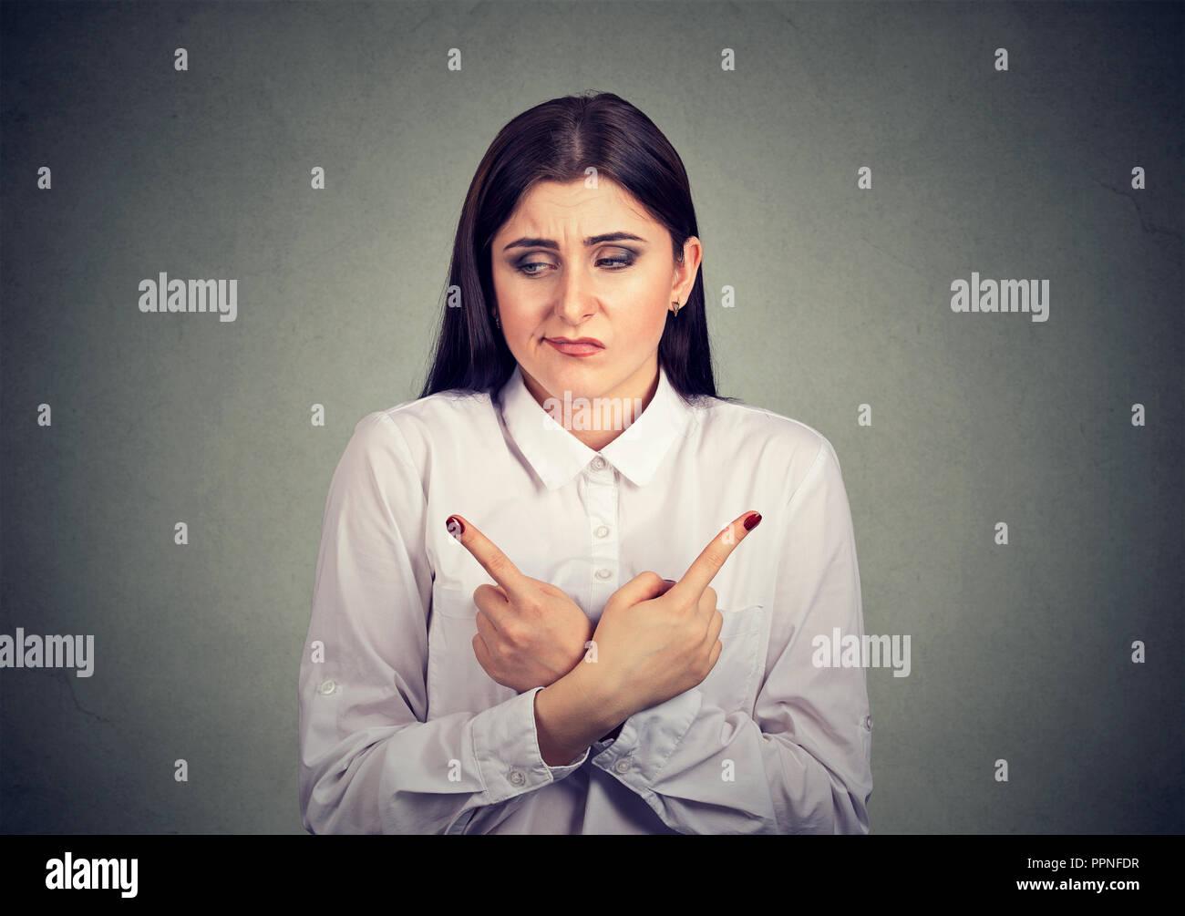 Jeune femme à la recherche a souligné l'incertitude tout en indiquant avec les doigts dans des directions opposées sur fond gris Photo Stock