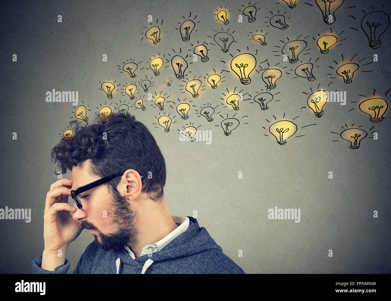 Jeune homme penser à avoir concentré beaucoup d'idées avec des ampoules lumineuses en toile de fond. Photo Stock
