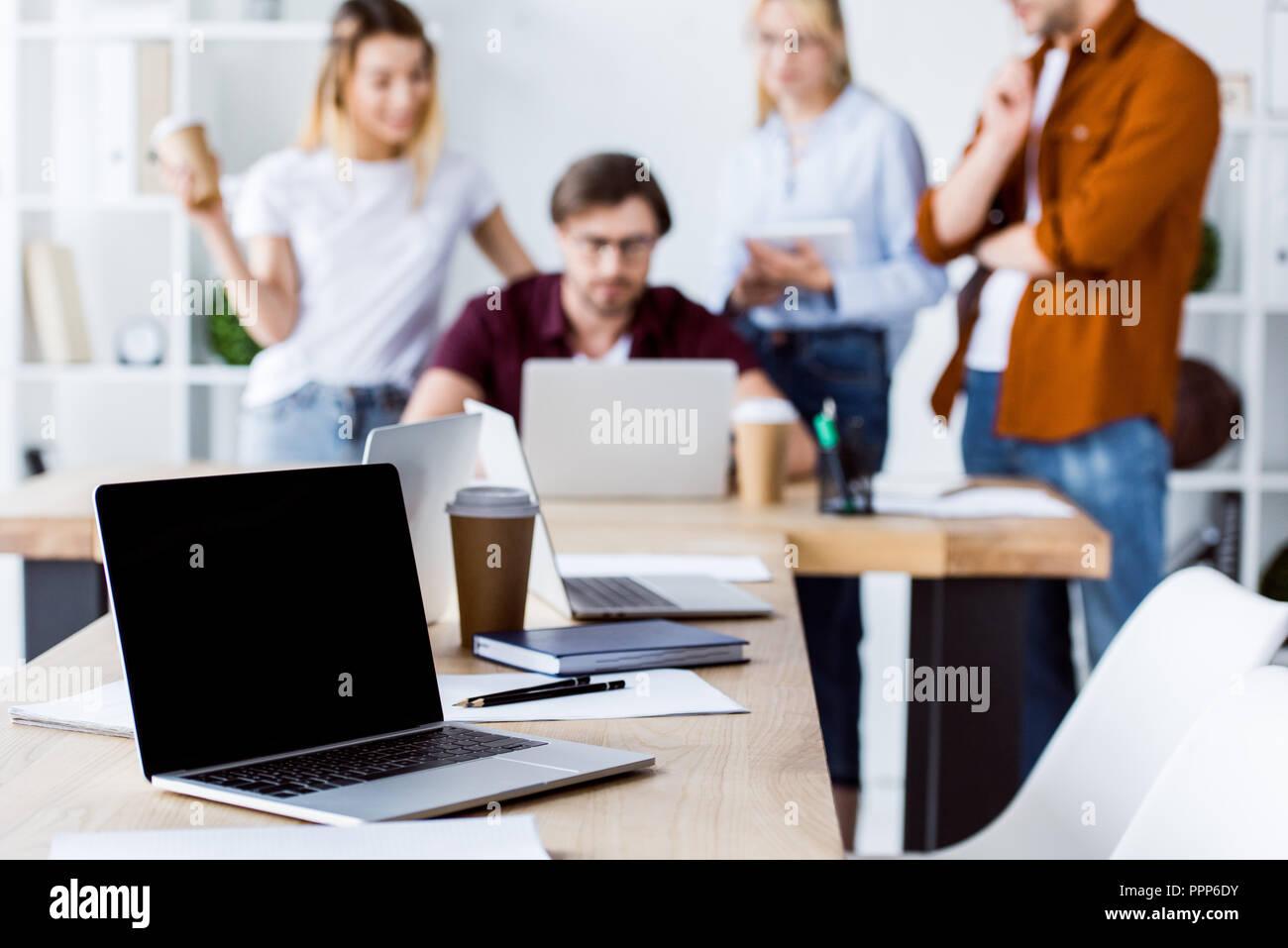 Des collègues qui travaillent sur des projets de démarrage en bureau avec ordinateur portable en premier plan Photo Stock