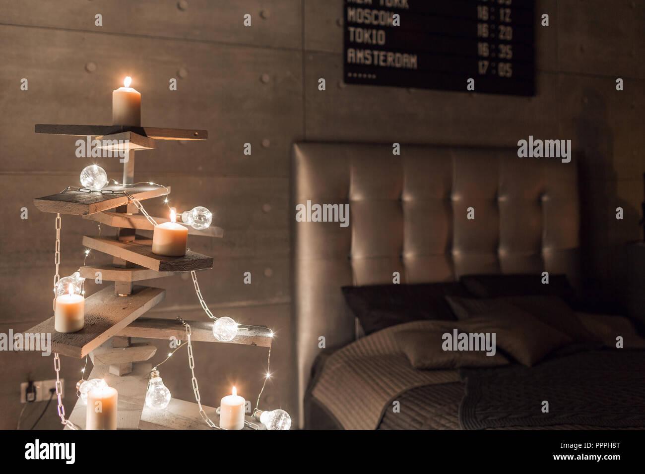 Arbre de Noël en bois de remplacement. Un arbre de Noël fait main et ampoule électrique sur le plancher dans la chambre Photo Stock