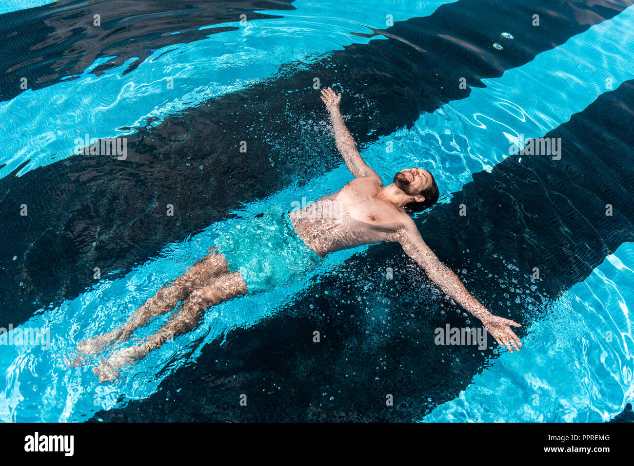 Homme barbu floating in swimming pool Photo Stock