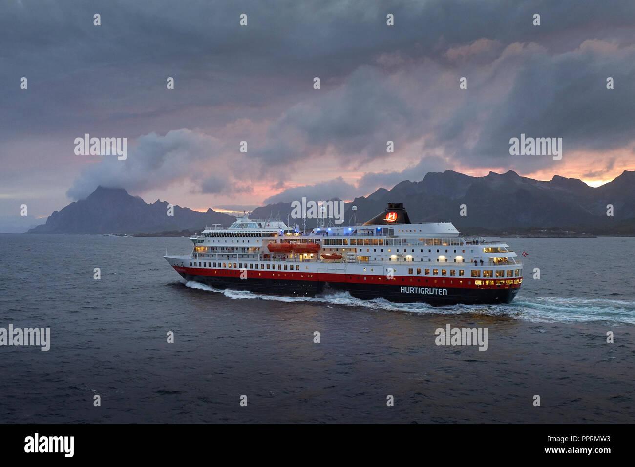 Le ferry Hurtigruten, MS FINNMARKEN, en direction du sud depuis Svolvær. Les montagnes spectaculaires des îles Lofoten et le soleil de minuit derrière la Norvège. Banque D'Images