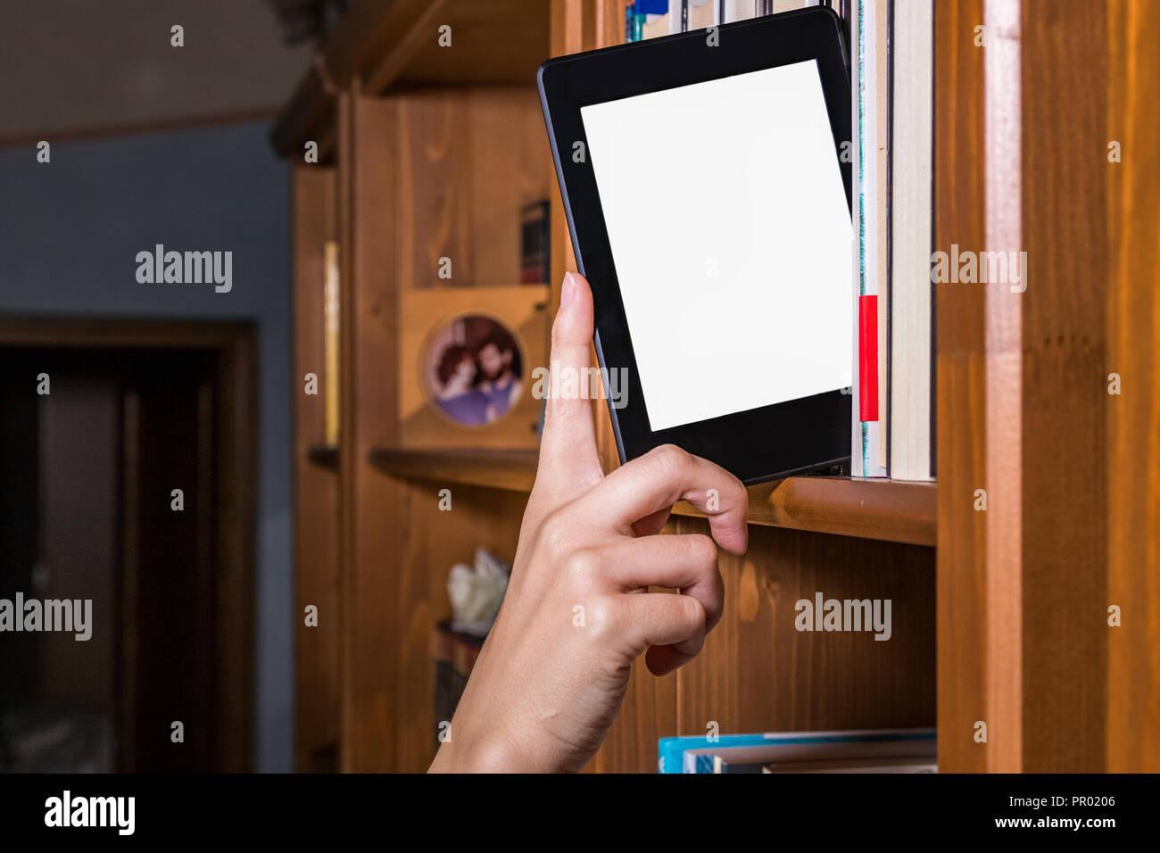 Main femme choisissant e reader parmi les livres sur une étagère Photo Stock