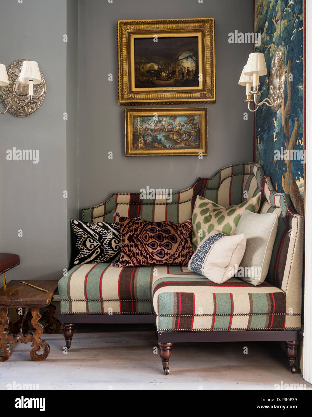 Les illustrations encadrées avec cadre doré 19e siècle tapisserie de verdure et Panneaux capitonnés banquette avec Andrew Martin stripe Photo Stock