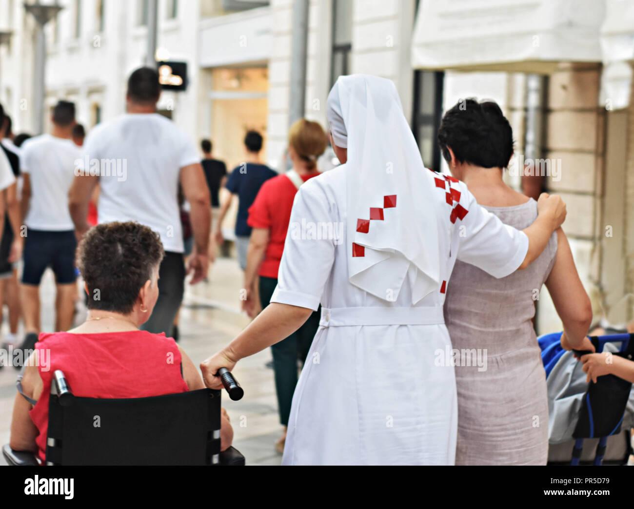 Christian nun marche sur la rue et aider woman in wheelchair Photo Stock