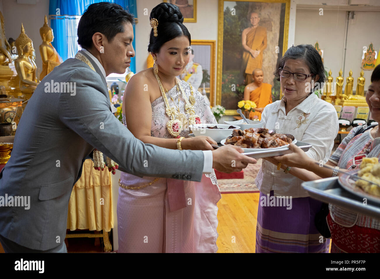 Jeunes mariés à un temple bouddhiste participer à la tradition où la congrégation se nourrir les moines. Dans le Queens, New York. Photo Stock