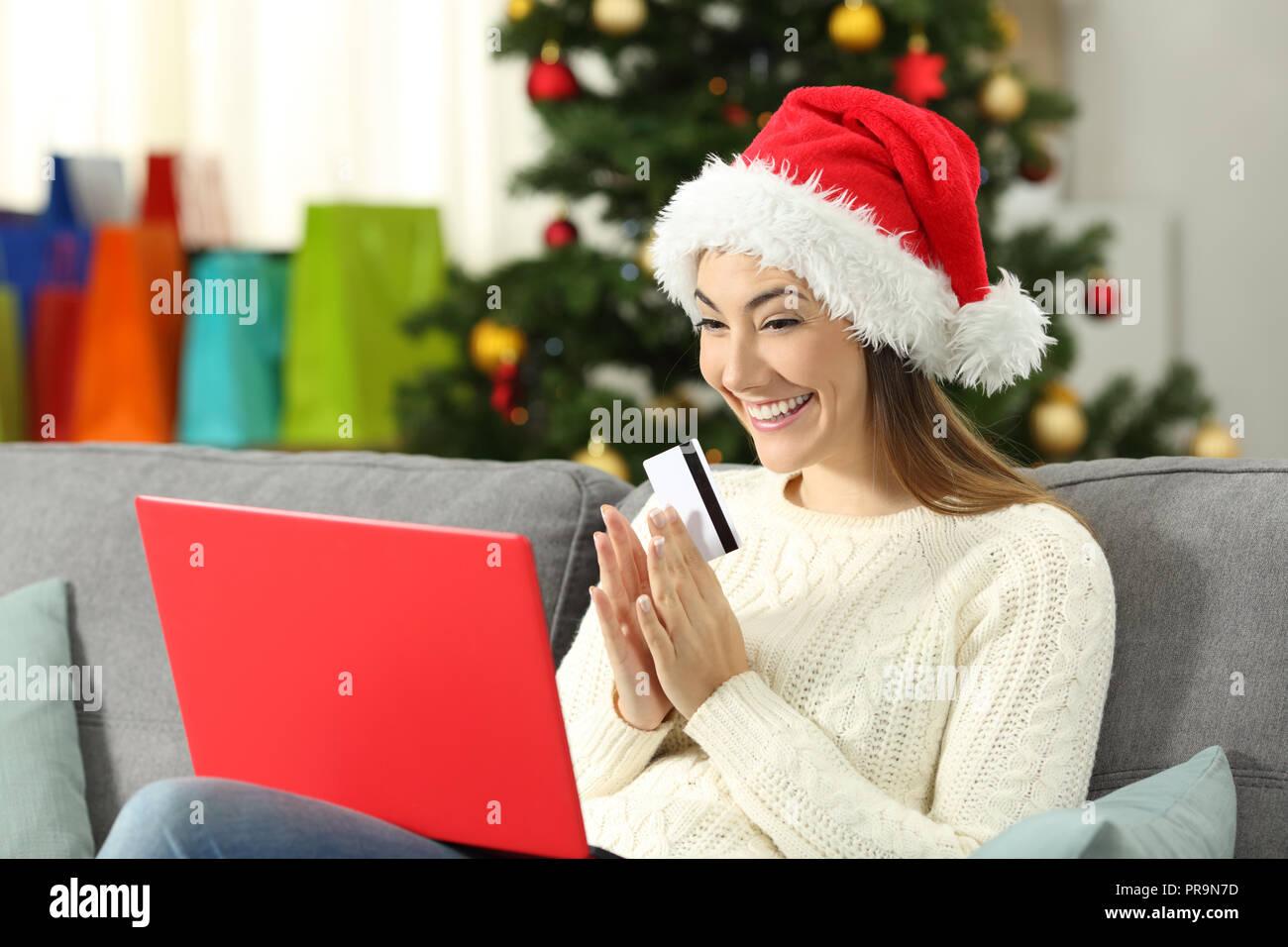 de32a9713bba2 Femme excité l'achat de cadeaux en ligne de Noël assis sur un canapé dans