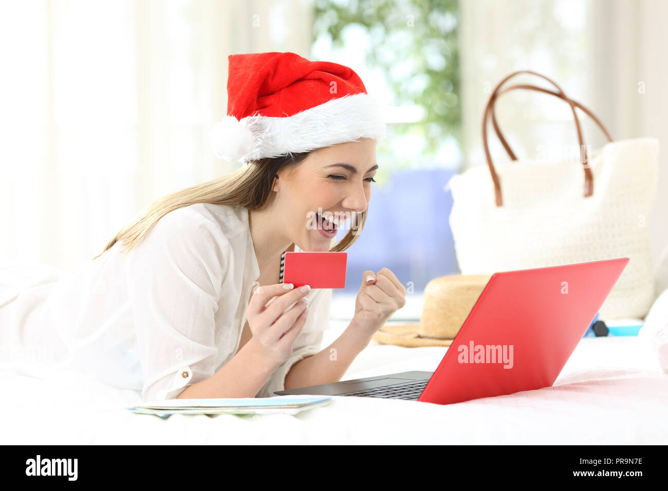 27ac93d794279 Femme excité l'achat en ligne sur vacances de Noël allongé sur un lit dans