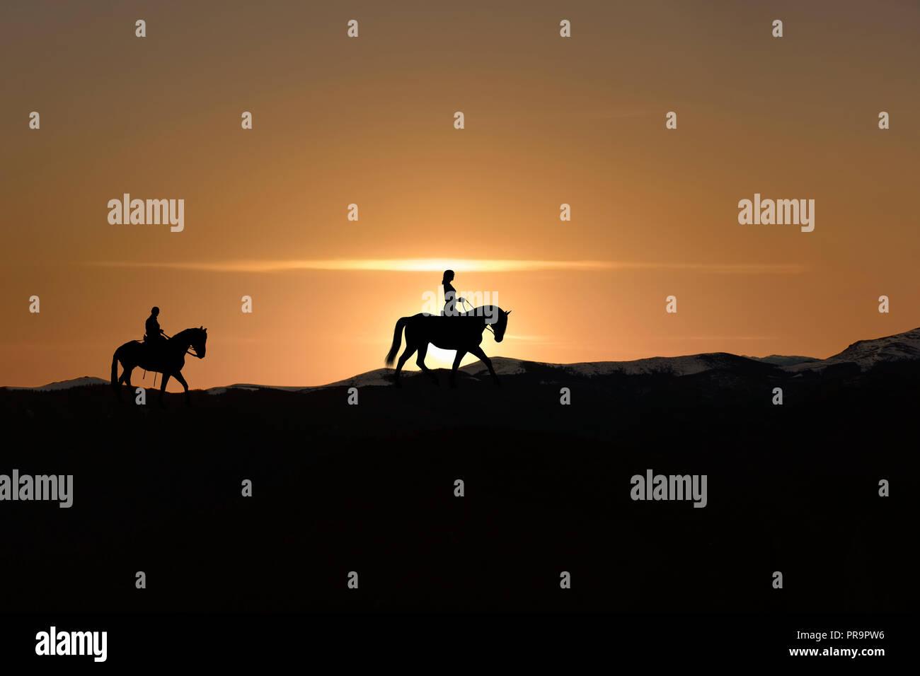 Silhouette of man and woman riding horse sur horizon comme le soleil se couche Banque D'Images