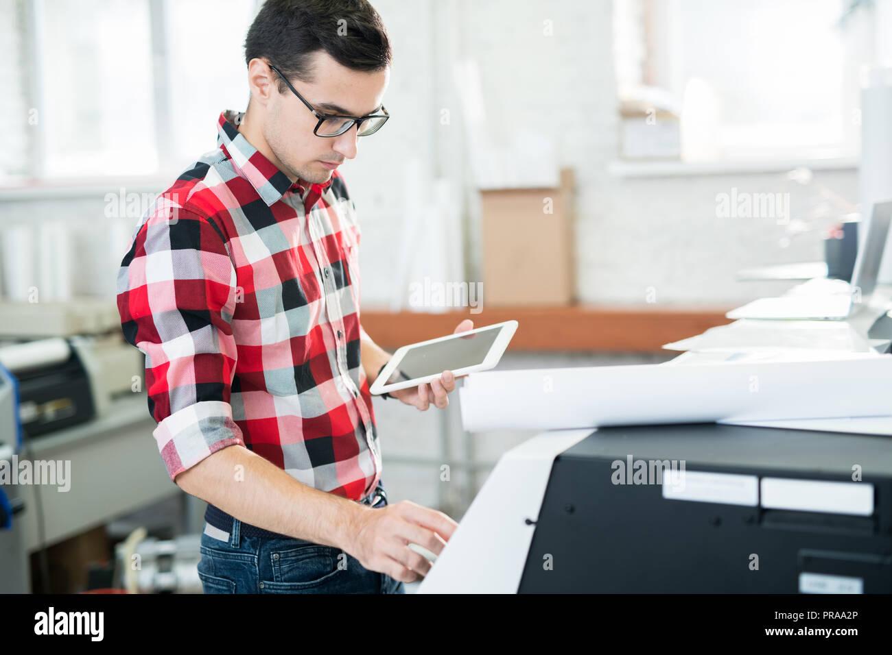 Occupé technicien travaillant avec imprimante Photo Stock