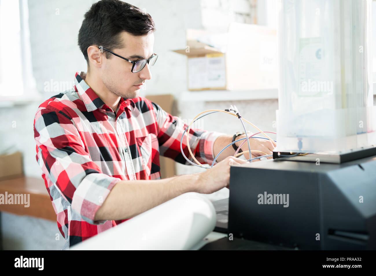 Ingénieur chargé de la réparation de l'imprimante de bureau dans le domaine de l'impression Photo Stock