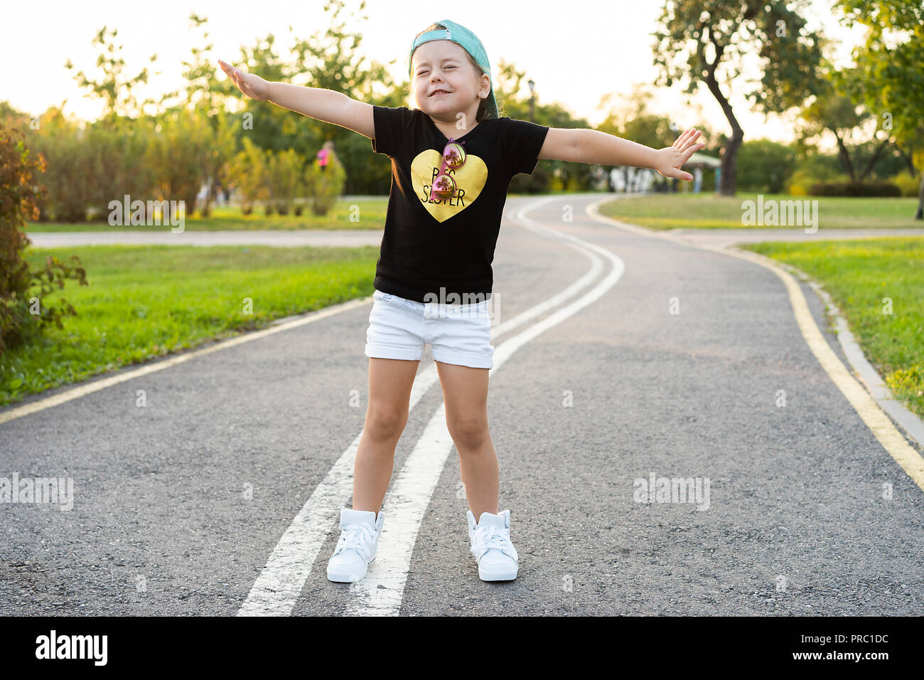 Fashion kid concept - portrait de petite fille mignonne enfant élégante portant une casquette à l'extérieur de la ville. Banque D'Images