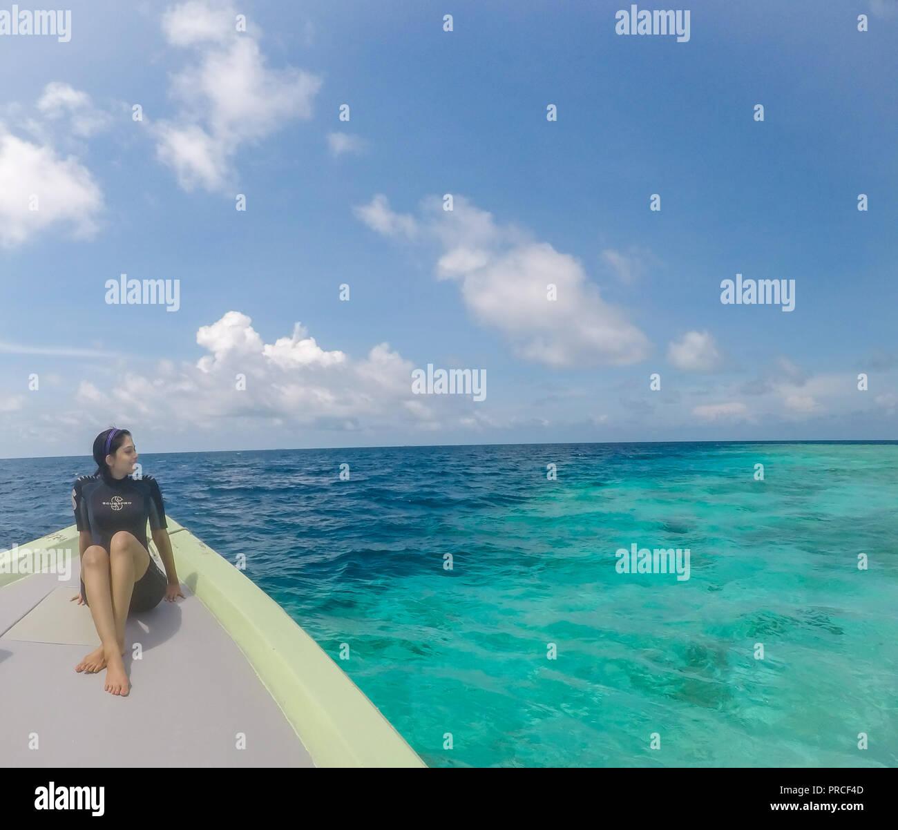 Fille assise dans un costume de plongée aux Maldives donnant sur l'océan Photo Stock