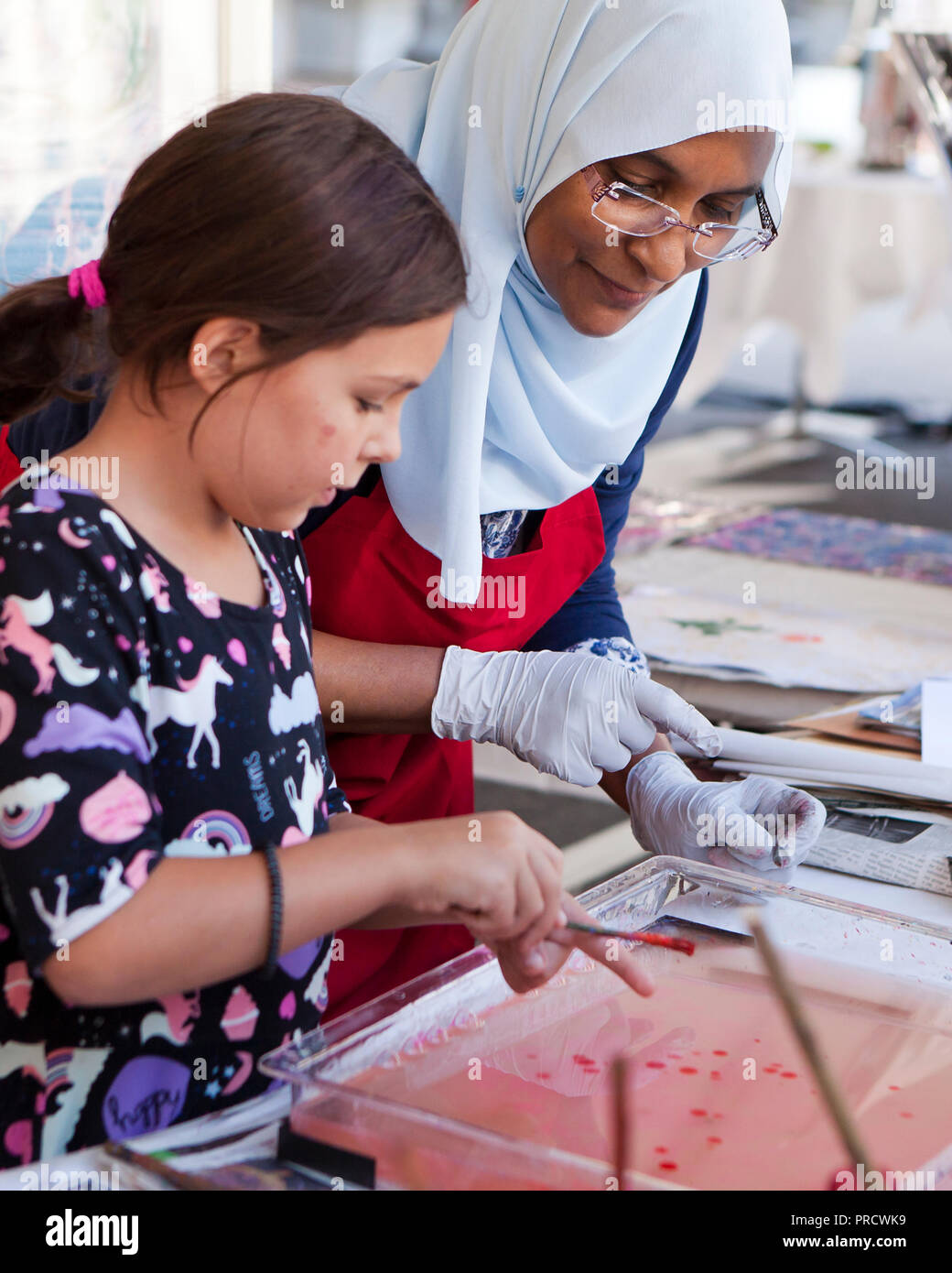 Femme musulmane aidant écolière avec art project - USA Photo Stock