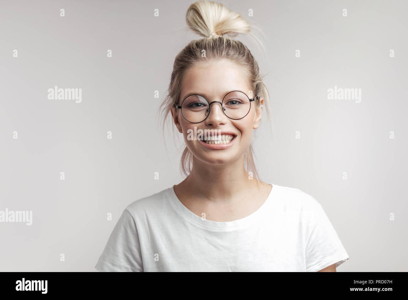 Happy smiling woman with Blonde hair bun pose seul contre fond blanc. Photo Stock