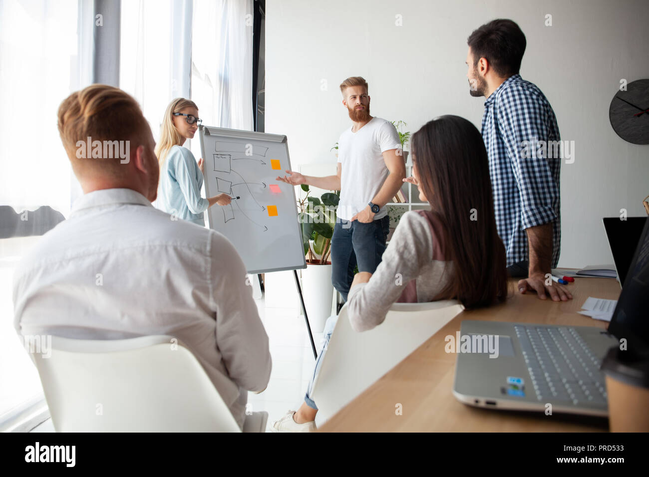 L'élaboration de nouvelle stratégie. Deux jeunes collègues effectuant présentation tout en travaillant avec leur équipe d'affaires dans le bureau. Photo Stock