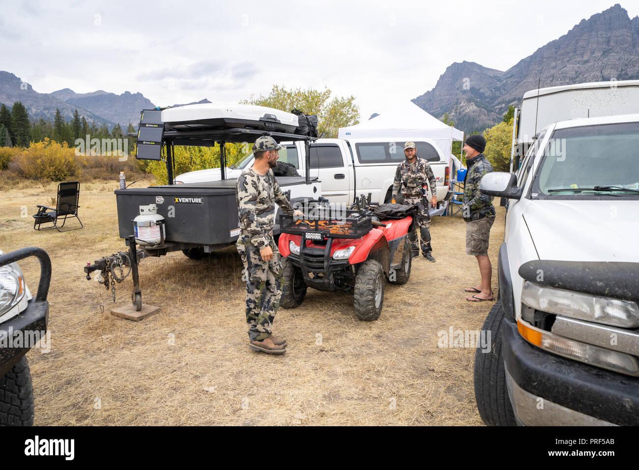 Les chasseurs mâles adultes se rassemblent autour de camp de base, de discuter de projets pour la journée. Les Camions et 4x4 roues dans la photo. Le port de camouflage Photo Stock